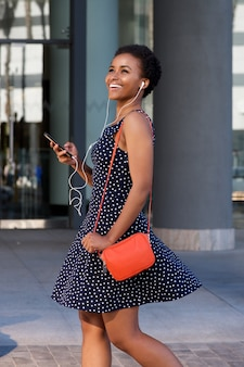 Femme noire souriante marchant et écoutant de la musique sur les écouteurs
