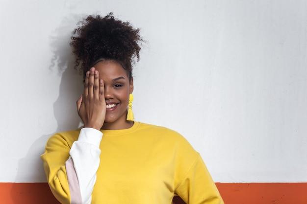 Femme noire souriante en tenue jaune couvrant les yeux avec la main