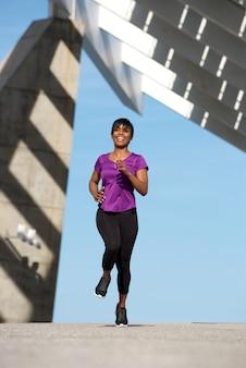Femme noire sportive pleine de corps courir en plein air et souriant