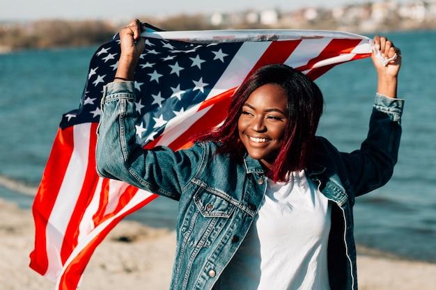 Femme noire tenant un drapeau américain au-dessus de la tête