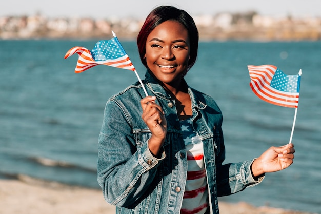 Femme noire, tenant drapeaux américains, dans, mains