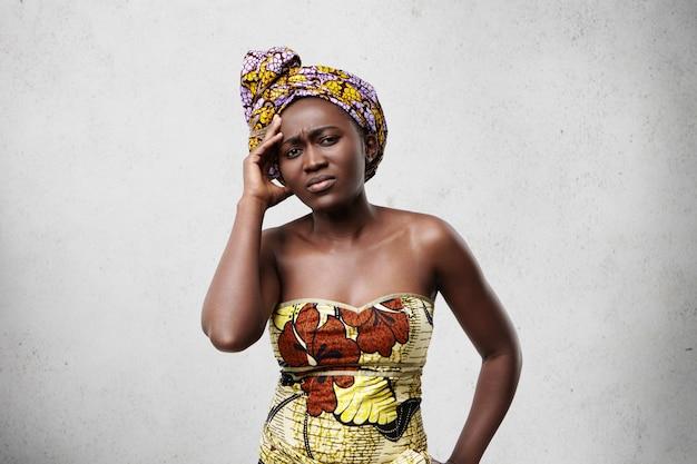 Femme noire triste avec des yeux profonds et des lèvres pleines portant un foulard et une robe tenant la main sur le temple ayant mal à la tête