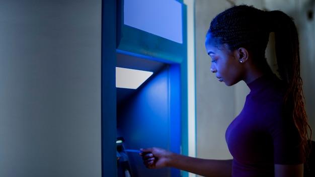 Femme noire utilisant le guichet automatique