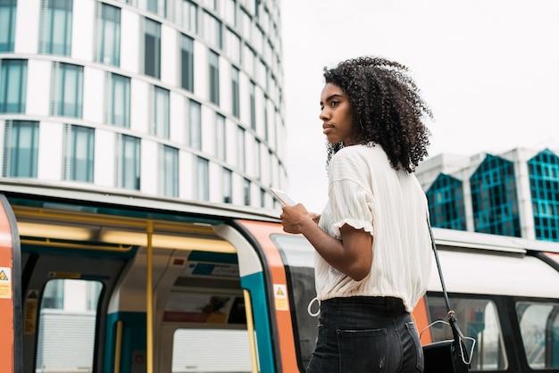 Femme noire, utilisation, téléphone portable, à, londres, souterrain