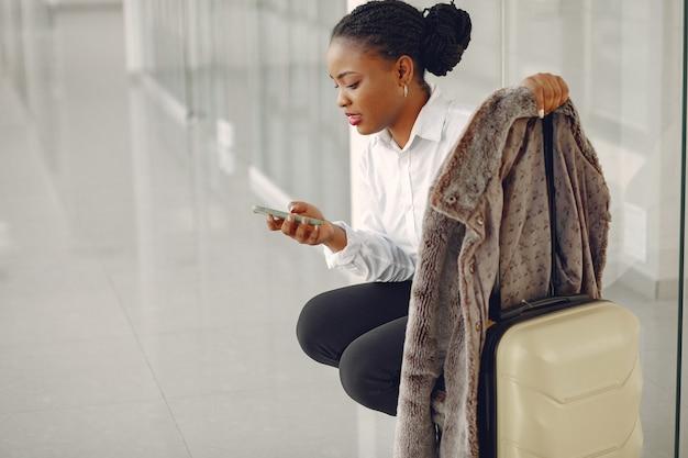Femme noire avec valise à l'aéroport