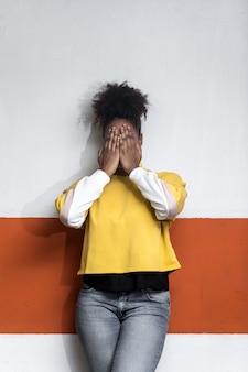 Femme noire en vêtements à la mode couvrant le visage