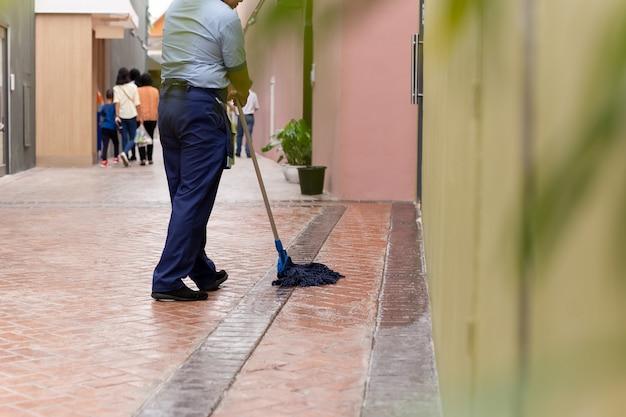 Femme non identifiée nettoyant un sol carrelé avec une vadrouille.