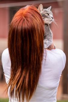 Femme non reconnue tenant son chat dans le jardin et le regardant.