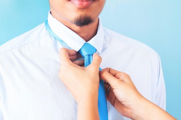 Femme nouant la cravate de son mari, gros plan, homme asiatique à la barbe