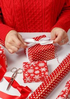 Femme noue un noeud de ruban sur un cadeau enveloppé close up