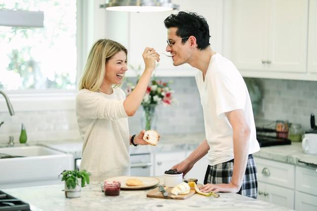 Femme nourrissant sa confiture de mûres à son petit ami