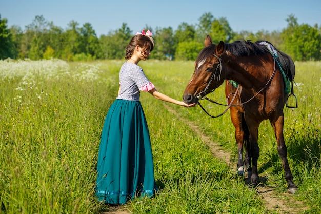 Femme nourrit un cheval avec les mains animal préféré
