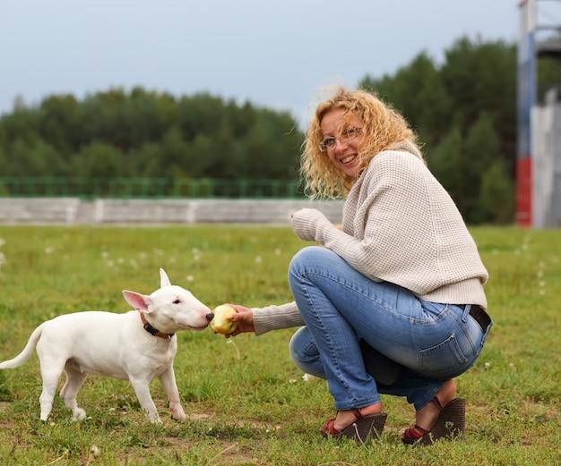 Une femme nourrit un chien un os