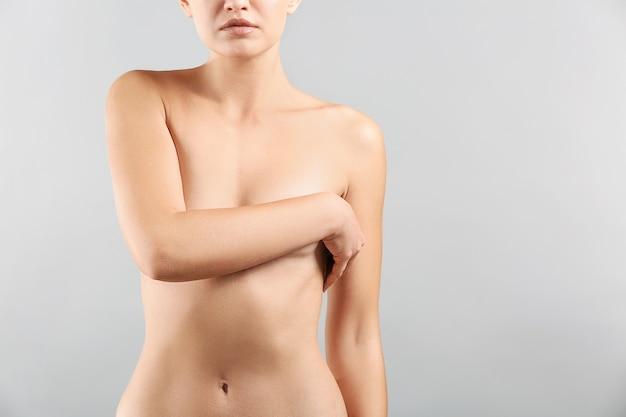 Femme nue sur gris. concept d'augmentation mammaire
