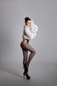 Femme nue sexy en collants avec de longues jambes posant sur un fond blanc. corps nu parfait, fesses fermes. femme séduisante, flirter