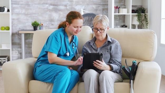 Femme nuse aidant une femme âgée à la retraite à utiliser sa tablette dans une maison de soins infirmiers