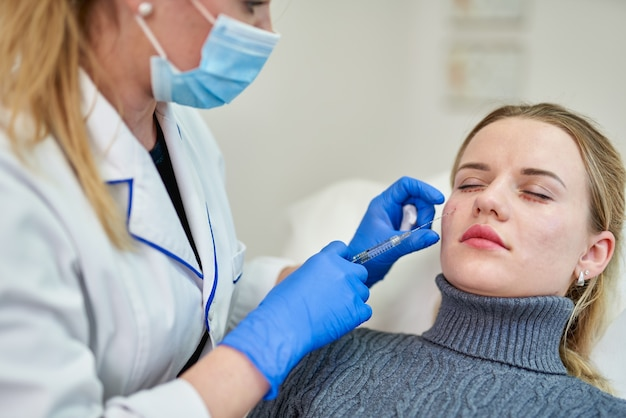Femme obtenant une injection cosmétique de botox près des yeux, gros plan