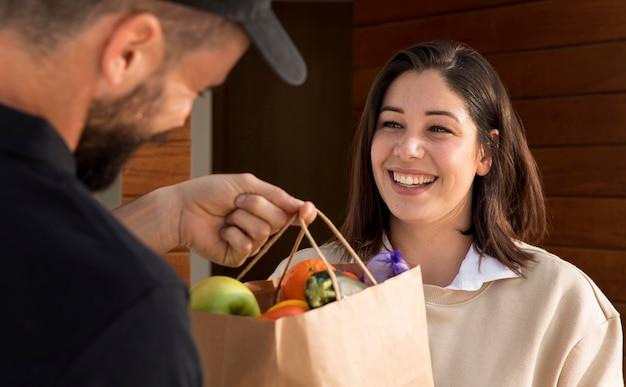 Femme obtenant un sac de nourriture livré