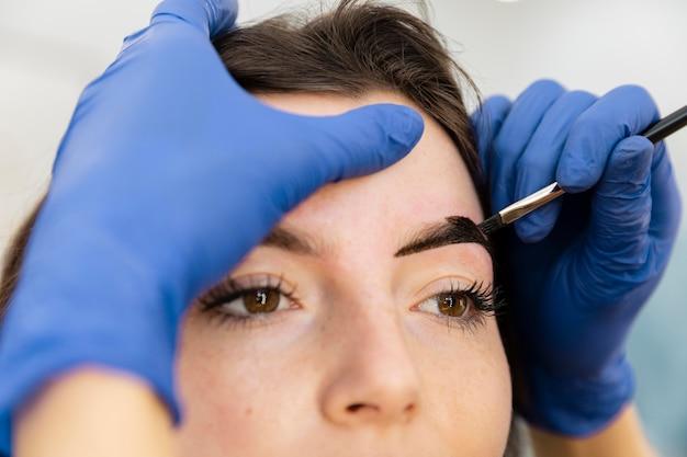 Femme obtenant un traitement des sourcils dans un salon de beauté