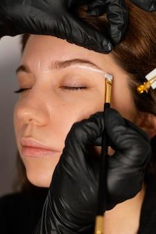 Femme obtenant un traitement des sourcils de l'esthéticienne