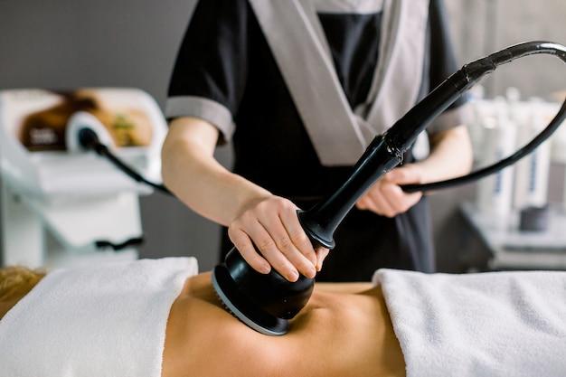 Femme, obtenir, anti, cellulite, et, anti, graisse, thérapie, dans, salon beauté. femme et mains de médecin cosmétologue au salon de médecine.