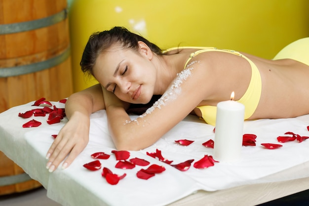 Femme obtenir un traitement de gommage au sel dans un salon spa