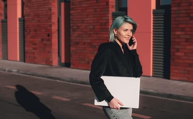 Femme occupée aux cheveux bleus marche tout en tenant son ordinateur portable et en discutant au téléphone
