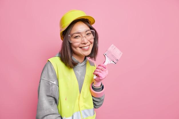 Une femme occupée à des travaux de rénovation et de rénovation porte des vêtements de sécurité tient un pinceau