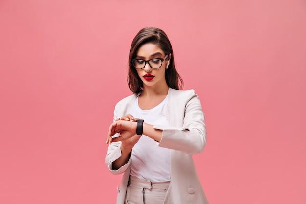 Femme occupée en veste beige regarde sa montre à main. brunette avec des lèvres brillantes rouges dans des verres et des écouteurs blancs posant sur fond isolé.