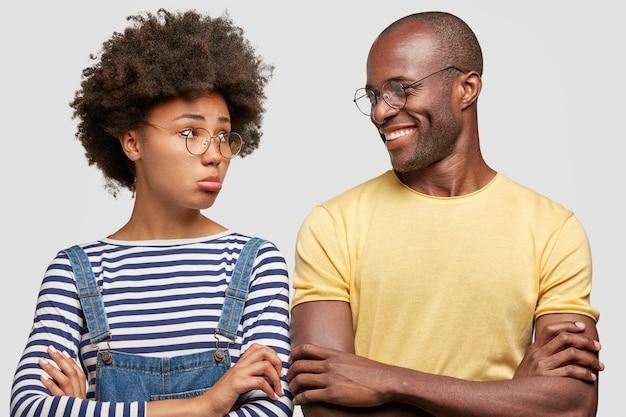 Une femme offensée serre les lèvres, garde les bras croisés, vêtue d'une chemise rayée, a une coiffure afro
