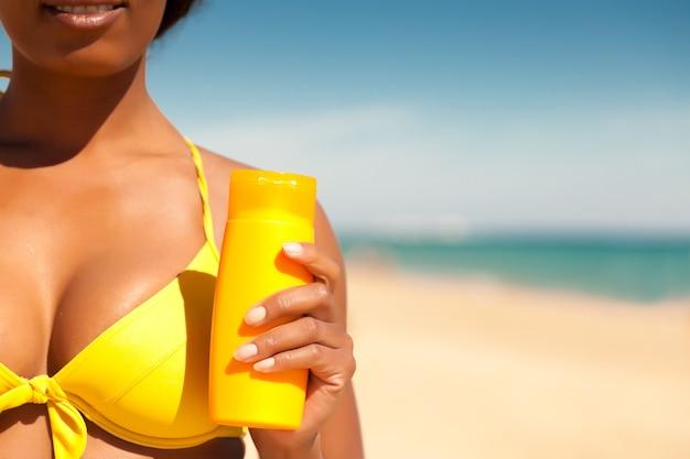 Femme offrant de la crème solaire sur la plage
