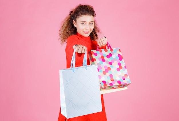Femme offrant des sacs colorés à son amie.