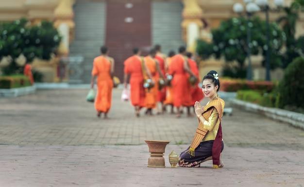 Une femme offre des offrandes de nourriture à des moines bouddhistes