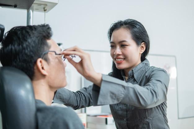 La femme ophtalmologiste applique le cadre expérimental au patient dans la clinique