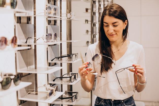Femme ophtalmologiste démontrant des lunettes dans une boutique d'opticien