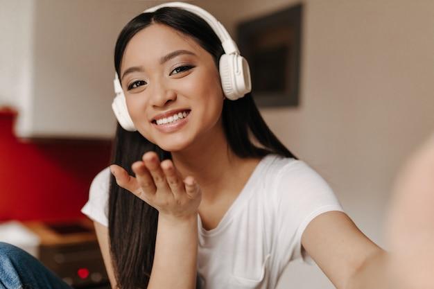 Femme optimiste dans les écouteurs et t-shirt blanc sourit, souffle baiser et prend des selfies dans la cuisine