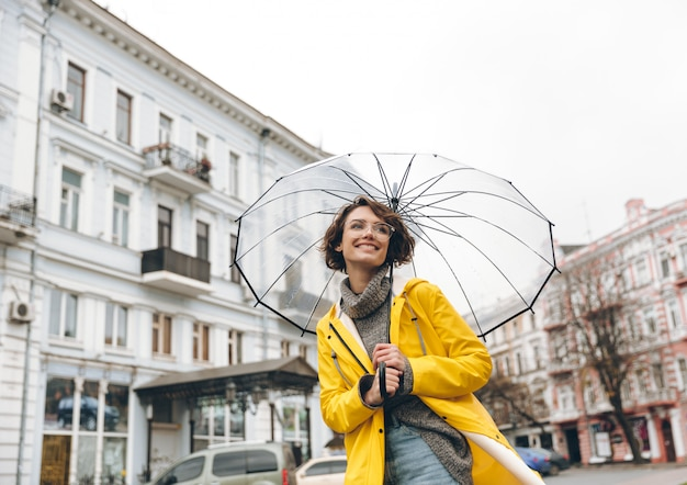 Femme optimiste en imperméable jaune et lunettes s'amuser en marchant à travers la ville sous un grand parapluie transparent pendant la froide journée pluvieuse