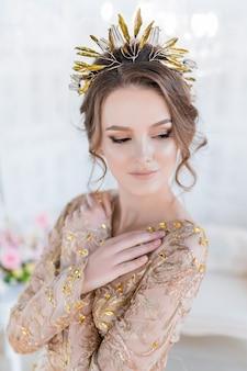 Femme en or soirée gawn et couronne pose dans la chambre blanche de luxe