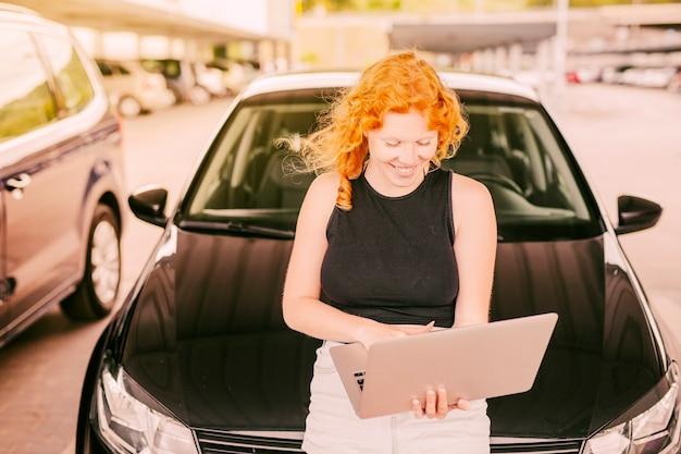 Femme avec ordinateur portable assis sur le capot de la voiture