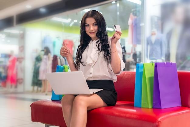 Femme avec ordinateur portable et carte de crédit au centre commercial