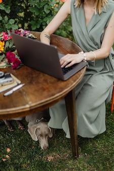 Femme avec un ordinateur portable dans le jardin travaillant avec son chien
