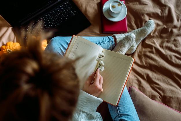 Femme avec un ordinateur portable dans ses mains, assis sur le lit.