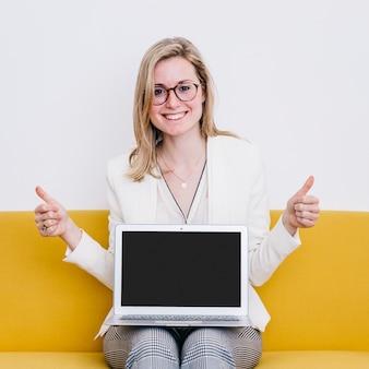 Femme avec ordinateur portable gesticulant thumb-up