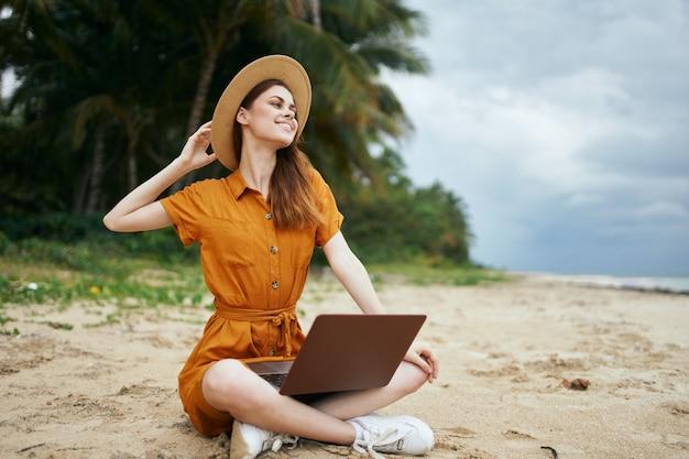 Femme avec ordinateur portable près de l'océan sur l'île sur le sable sur la plage