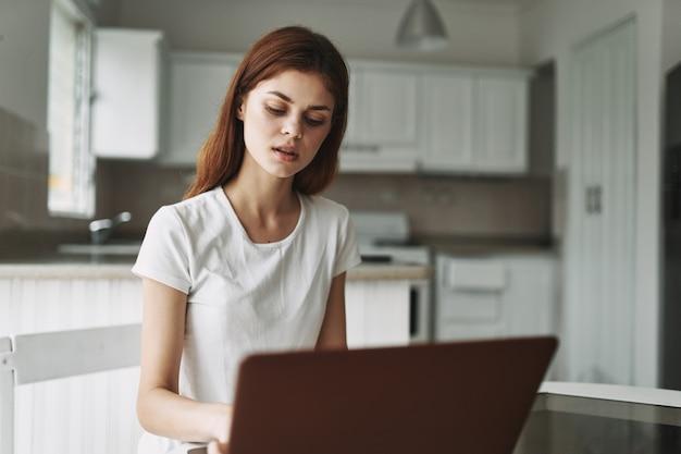 Femme avec ordinateur portable à table pigiste travaillant à l'extérieur de la salle intérieure du bureau