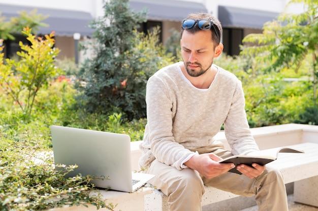 Femme avec ordinateur portable et tablette travaillant à l'extérieur