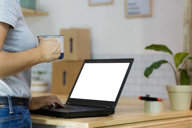 Femme avec un ordinateur portable et une tasse de café