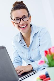 Femme avec un ordinateur portable travaillant à la maison