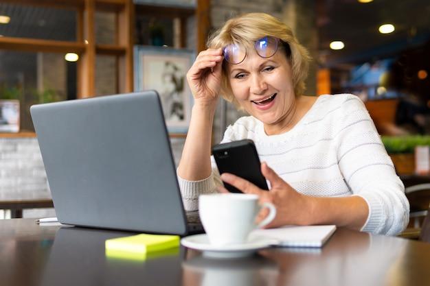 Une femme avec un ordinateur portable travaille dans un bureau. la femme d'âge moyen est une femme d'affaires. elle est au téléphone, souriante.
