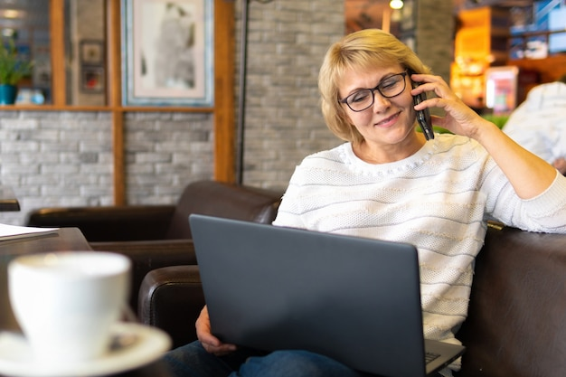 Une femme avec un ordinateur portable travaille dans un bureau